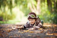 有飞行员帽子的小男孩,说谎在地面上在公园 免版税图库摄影