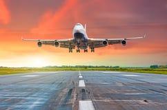 有飞行在一条跑道的四个引擎的大远程飞机到来着陆在晚上在明亮的红色日落期间 免版税图库摄影