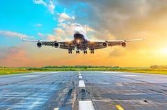有飞行在一条跑道的四个引擎的航空器到来着陆在晚上在明亮的红色梯度日落期间 免版税库存图片