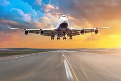 有飞行在一条跑道的四个引擎的飞机到来着陆在晚上在明亮的红色日落期间 库存图片