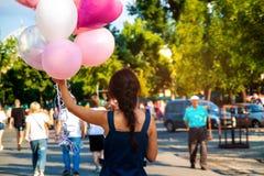 有飞行多彩多姿的气球的年轻亚裔美女在城市 免版税库存照片