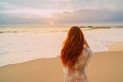 有飞行头发的在海洋,背面图年轻红发妇女 免版税库存照片