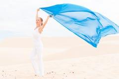 有飞行的蓝色围巾少妇 免版税库存图片