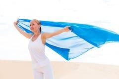 有飞行的蓝色围巾少妇 免版税库存照片