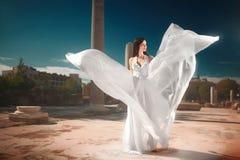 有飞行的飘渺,神的新娘,站立在临时雇员的发光的礼服 库存图片