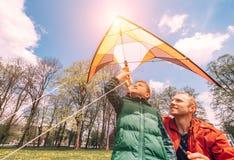 有飞行风筝的儿子开始的父亲 库存图片