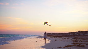 有飞行风筝的可爱的小女孩在热带海滩 在海洋岸的孩子戏剧 有海滩玩具的孩子 股票录像