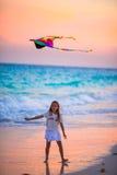 有飞行风筝的小女孩在日落的热带海滩 在海洋岸的孩子戏剧与海滩戏弄 免版税图库摄影