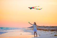 有飞行风筝的小女孩在日落的热带海滩 在海洋岸的孩子戏剧 有海滩玩具的孩子 免版税库存照片