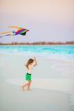 有飞行风筝的小女孩在热带海滩 在海洋岸的孩子戏剧 有海滩玩具的孩子 库存照片