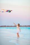 有飞行风筝的小女孩在热带海滩 在海洋岸的孩子戏剧 有海滩玩具的孩子 库存图片