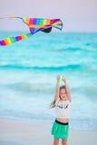 有飞行风筝的小连续女孩在热带海滩 在海洋岸的孩子戏剧 有海滩玩具的孩子 免版税图库摄影
