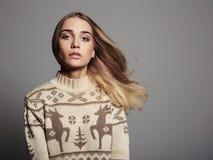 有飞行头发的美丽的妇女在冬天套头衫 秀丽白肤金发的女孩 免版税库存照片