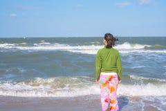有飞行头发的运动的妇女在海浪站立 库存图片