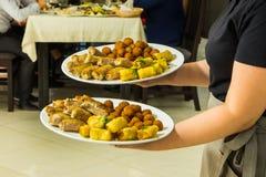 有食物盘服务宴会桌的女服务员 免版税图库摄影