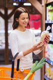 有食物篮子的愉快的少妇在市场上 库存图片