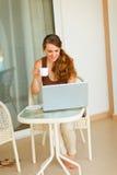 有食用的膝上型计算机的微笑的妇女茶 免版税库存图片
