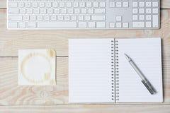有餐巾和键盘的白色书桌 库存图片