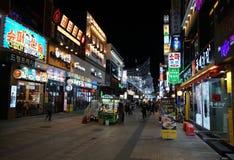 有餐馆、酒吧和许多五颜六色的广告牌标志的典型的韩国步行区域 免版税库存图片