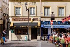 有餐馆和夏天大阳台的巴黎人街道 图库摄影