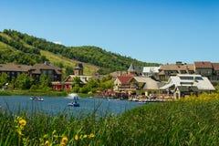 有餐馆和池塘的蓝色山村 免版税库存照片