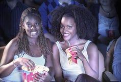 有饮料和玉米花观看的电影的女性朋友在剧院 图库摄影