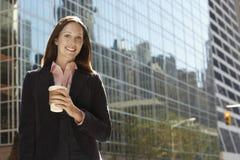 有饮料外部办公楼的女实业家 免版税图库摄影