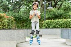 有饮料的亚裔女孩在溜冰鞋 库存图片