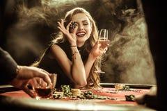 有饮料的微笑的妇女和打扑克的纸牌筹码 图库摄影
