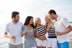 有饮料的微笑的朋友在海滩的瓶 图库摄影