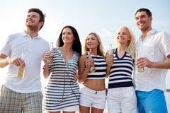 有饮料的微笑的朋友在海滩的瓶 库存图片