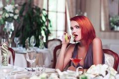 有饮料的性感的红头发人妇女 免版税库存照片
