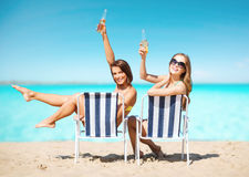 有饮料的愉快的少妇晒日光浴在海滩的 库存照片
