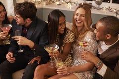 有饮料的朋友享受鸡尾酒会的小组  免版税库存图片