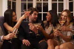 有饮料的朋友享受鸡尾酒会的小组  免版税库存照片