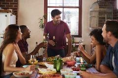 有饮料的朋友在晚餐会期间的桌上 免版税库存图片
