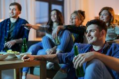 有饮料看着电视的愉快的朋友在家 图库摄影
