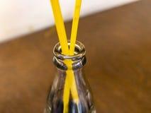 有饮用的管子的一个空的瓶在餐馆 免版税库存图片