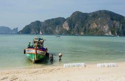 有饮用水卖主的木小船在热带海岛沙滩登陆了  库存照片