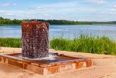 有饮用水的喷泉在湖在晴天 免版税库存图片