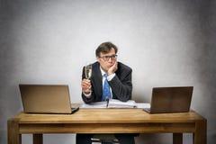 有香槟玻璃的孤独的商人 免版税图库摄影