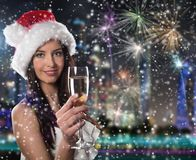 有香槟玻璃的年轻圣诞老人女孩 库存照片