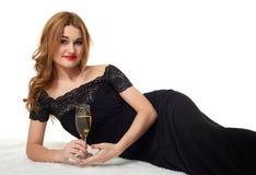 有香槟说谎在毛皮的杯的女孩,穿一件黑礼服 免版税库存照片