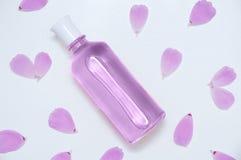 有香水和花瓣的玻璃瓶 免版税图库摄影
