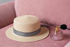 有香水的草帽在桃红色椅子时尚背景 库存照片