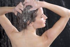 有香波的妇女洗涤的头 免版税库存照片