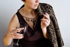 有香烟和一杯的美丽的妇女红葡萄酒 库存照片