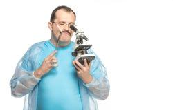 有香烟和显微镜的可笑肥胖外科医生 库存图片