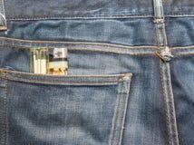 有香烟打火机的(在香烟打火机的焦点蓝色牛仔布牛仔裤) 库存图片