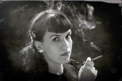 有香烟的减速火箭的妇女 库存图片